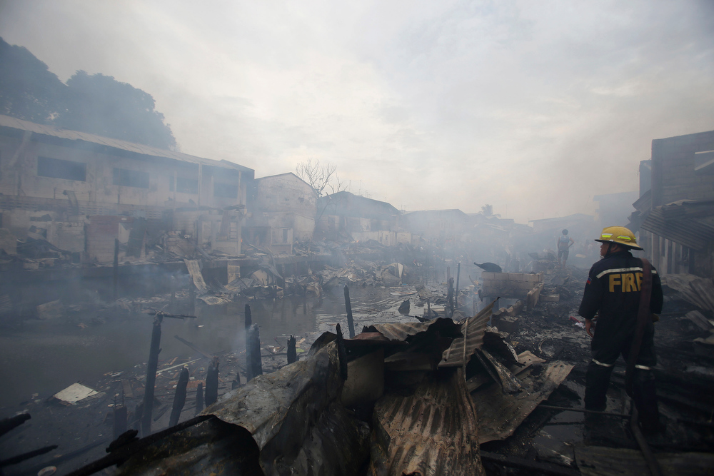 . A Filipino fireman checks the area where houses are still smoldering shortly after a fire broke out at a slum area in Pasay, south of Manila, Philippines on Wednesday, July 24, 2013. Pasay City Fire Marshall Major Douglas Guiyab said about 250 houses were gutted in the area and the cause of the fire is still being determined. (AP Photo/Aaron Favila)