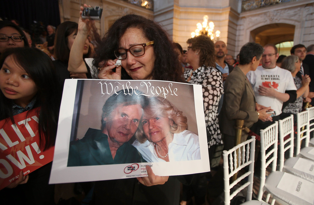 ". Melanie Nathan, of San Francisco, reacts after the Supreme Court\'s decision on Proposition 8 and the Defense of Marriage Act during a screening at City Hall in San Francisco, Calif., on Wednesday, June 26, 2013. Nathan holds a picture of Edith ""Edie\"" Windsor, right, and her late spouse Thea Spyer, plaintiffs in the DOMA case. The couple, whose marriage in Canada in 2007 was recognized in their home state of New York, were together for 44 years.The U.S. Supreme Court dismissed California\'s Proposition 8 and declared the 1996 Defense of Marriage Act unconstitutional. (Jane Tyska/Bay Area News Group)"
