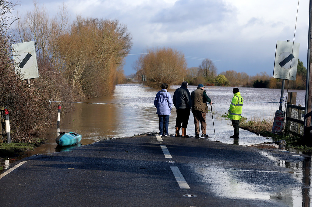 . People look at flood waters close to the village of East Lyng that has blocked the main A361 road on February 13, 2014 in Somerset, England.  (Photo by Matt Cardy/Getty Images)