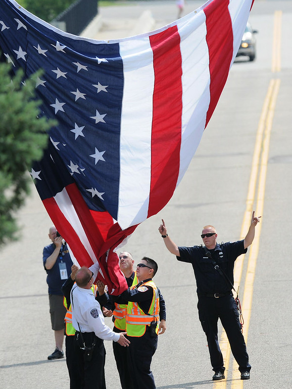 . A flag is raised on Acacia Boulevard hours before the procession enters Acacia Park Cemetery in Mendota Heights for the burial of officer Scott Patrick.  (Pioneer Press: Jean Pieri)