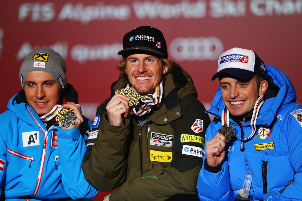 Description of . Race winner Ted Ligety (C) of the United States of America celebrates with second placed Marcel Hirscher (L) of Austria and third placed Manfred Moelgg (R) of Italy at the medal ceremony following the Men\'s Giant Slalom during the Alpine FIS Ski World Championships on February 15, 2013 in Schladming, Austria.  (Photo by Clive Mason/Getty Images)