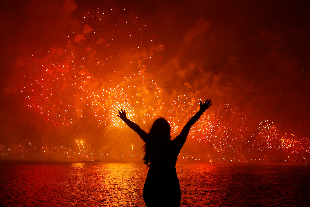 . A woman celebrates the New Year as she watches fireworks exploding above Copacabana beach in Rio de Janeiro January 1, 2013. More than two million people gathered along Rio\'s most famous beach to witness the 20-minute display and celebrate the beginning of a new year. REUTERS/Pilar Olivares