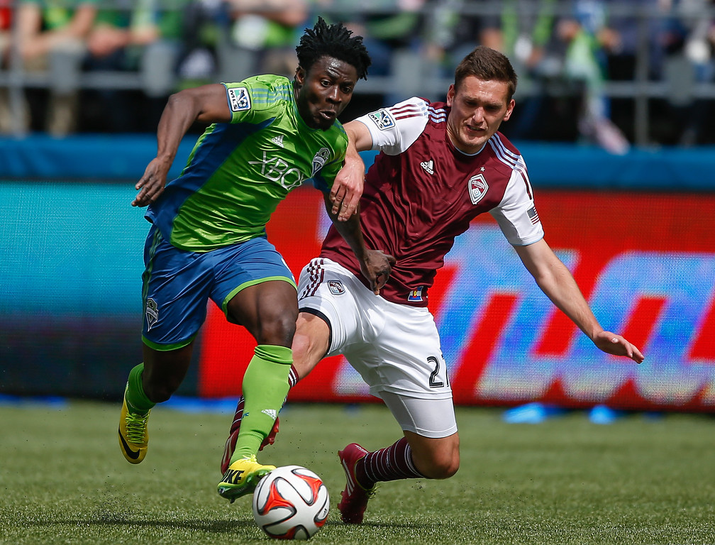 . Obafemi Martins #9 of the Seattle Sounders FC dribbles against Shane O\'Neill #27 of the Colorado Rapids at CenturyLink Field on April 26, 2014 in Seattle, Washington. The Sounders defeated the Rapids 4-1.  (Photo by Otto Greule Jr/Getty Images)