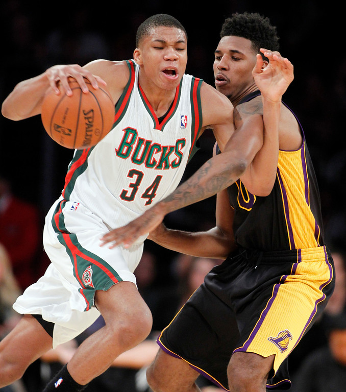 . Milwaukee Bucks guard Giannis Antetokounmpo (34) drives around Los Angeles Lakers forward Nick Young during the first half of an NBA basketball game Tuesday, Dec. 31, 2013, in Los Angeles. (AP Photo/Alex Gallardo)