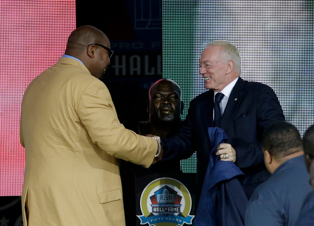 . Former NFL football player Larry Allen, left, shakes hands with presenter Dallas Cowboys owner Jerry Jones during the induction ceremony at the Pro Football Hall of Fame Saturday, Aug. 3, 2013, in Canton, Ohio. (AP Photo/Tony Dejak)