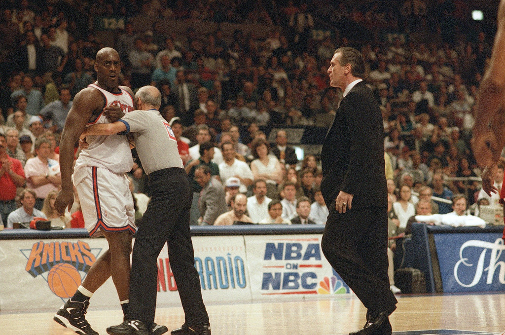 . New York Knicks forward Anthony Mason, left, is restrained by referee Dick Barerta, center, after Mason was involved in a scuffle at the end of the first half of Game 5 of the NBA Finals, at Madison Square Garden, Friday, June 17, 1994, New York. Knicks head coach Pat Riley tries to calm Mason down. (AP Photo/Amy Sancetta)
