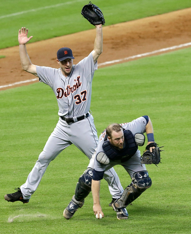 . Detroit Tigers starting pitcher Max Scherzer (37) stays out of the way as catcher Bryan Holaday scoops up the ball on a Houston Astros\' Jose Altuve ground-ball single in the fifth inning of a baseball game Saturday, June 28, 2014, in Houston. (AP Photo/Pat Sullivan)
