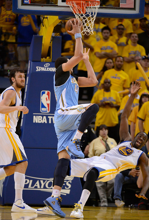 . JaVale McGee (34) of the Denver Nuggets goes up for a shot as he gets fouled by Draymond Green (23) of the Golden State Warriors late in the fourth quarter in Game 6 of the first round NBA Playoffs May 2, 2013 at Oracle Arena. (Photo By John Leyba/The Denver Post)