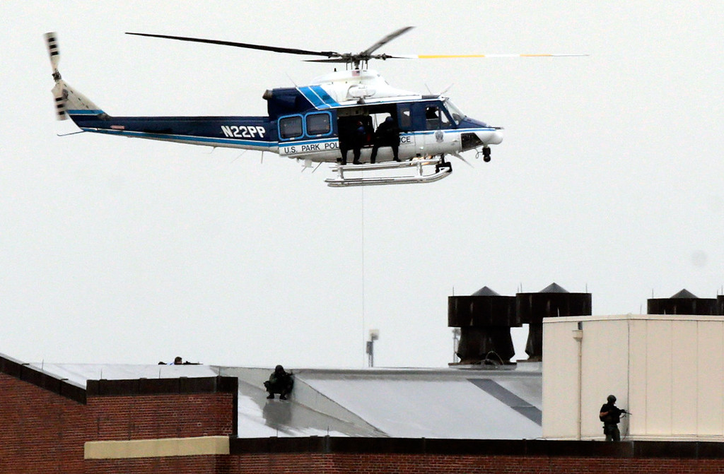 . A Park Police helicopter hovers above snipers on the roof of a building at the Navy Yard complex where a shooting took place early this morning September 16, 2013 in Washington, DC. Early reports indicate that several people may have been shot, and police are still trying to determine the number of suspects involved in the shooting. (Photo by Win McNamee/Getty Images)
