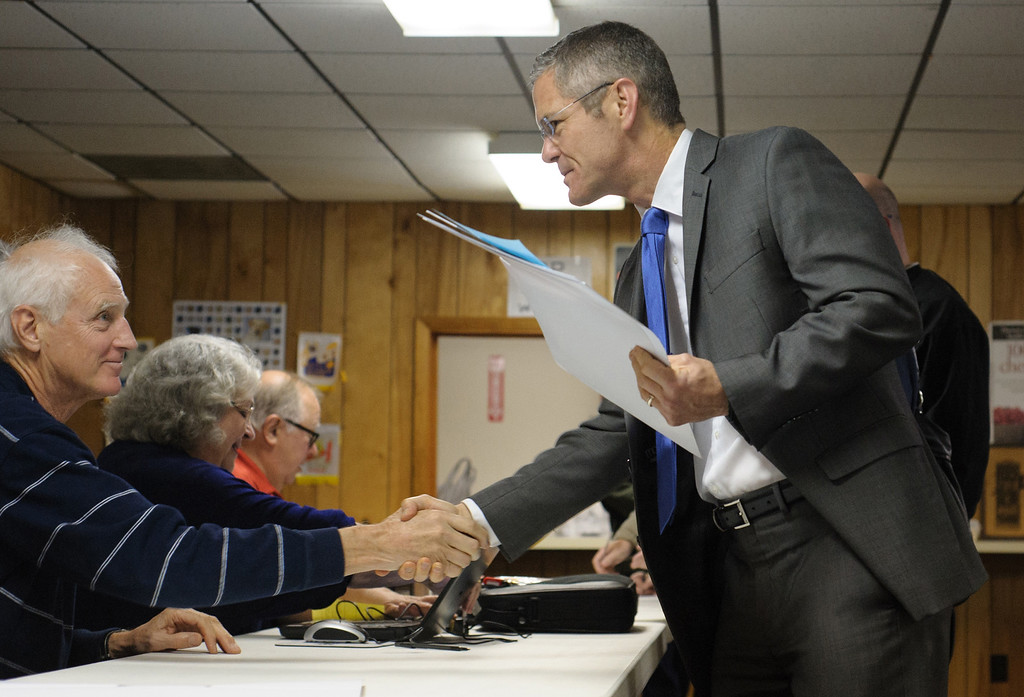. Mark Schauer, Democratic candidate for governor, speaks with precinct worker Steven Turner at the Bedford Lions Club, Tuesday, Nov. 4, 2014 in Battle Creek, Mich. Schauer is running against incumbent Gov. Rick Snyder. (AP Photo/Battle Creek Enquirer, Seth Graves)