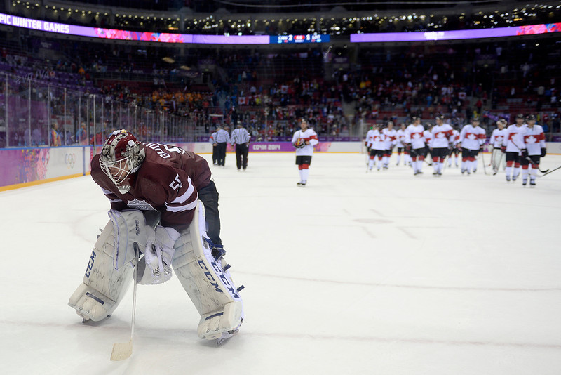 . Kristers Gudlevskis (50) of the Latvia skates off the ice as Canada celebrates after the third period of Canada\'s 2-1 win over Latvia. Sochi 2014 Winter Olympics on Wednesday, February 19, 2014 at Bolshoy Ice Arena. (Photo by AAron Ontiveroz/ The Denver Post)