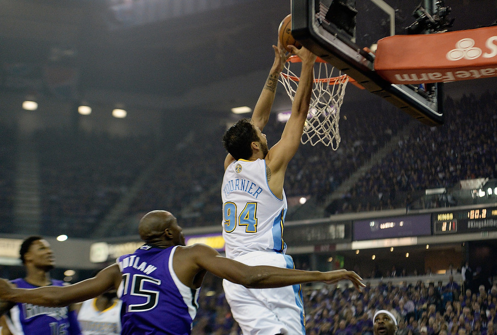 . SACRAMENTO, CA - OCTOBER 30:  Evan Fournier #94 of the Denver Nuggets scores in front of Travis Outlaw #25 of the Sacramento Kings during the second quarter at Sleep Train Arena on October 30, 2013 in Sacramento, California. NOTE TO USER: User expressly acknowledges and agrees that, by downloading and or using this photograph, User is consenting to the terms and conditions of the Getty Images License Agreement.  (Photo by Thearon W. Henderson/Getty Images)