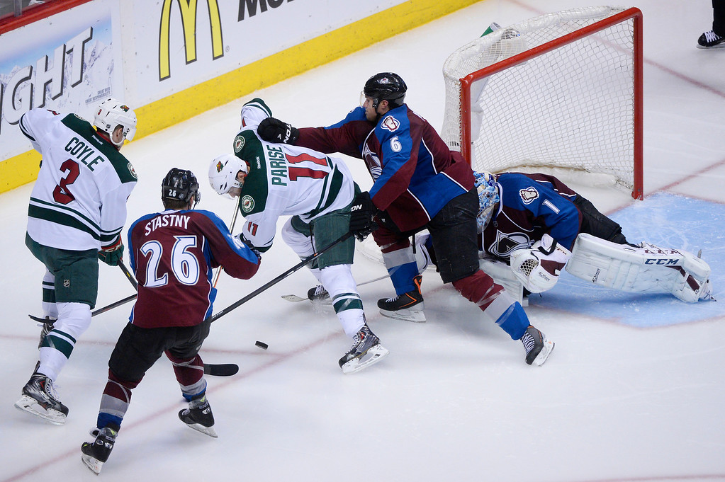 . Paul Stastny (26) and Erik Johnson (6) of the Colorado Avalanche fight for puck posession with Charlie Coyle (3) and Zach Parise (11) of the Minnesota Wild during overtime. (Photo by Karl Gehring/The Denver Post)