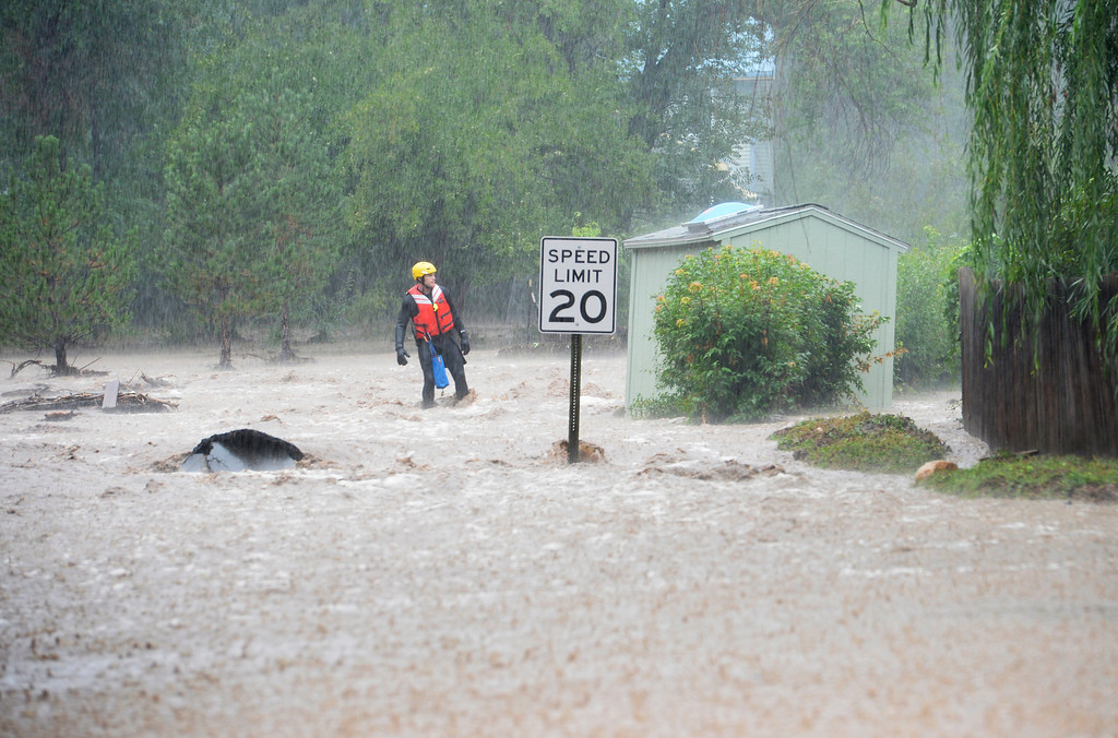 . BOULDER, CO - SEPTEMBER 12: A Rescue worker goes door to door checking on residents in north Boulder, September 12, 2013. Massive flash flooding is on going along the Front Range of Colorado. (Photo By RJ Sangosti/The Denver Post)