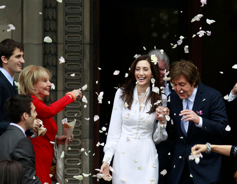 . American broadcast journalist and author Barbara Walters throws rose petals as former Beatle Sir Paul McCartney and his wife American heiress Nancy Shevell leave Marylebone Registry Office, following their wedding in central London , Sunday Oct. 9, 2011.  Shevell, 51, is McCartney\'s third wife.The couple met in the Hamptons in Long Island, New York, shortly after the singer\'s divorce from Heather Mills in 2008 and they were engaged earlier this year. (AP Photo/Lefteris Pitarakis)