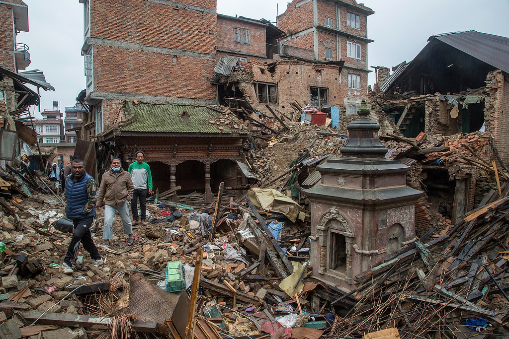 . Residents cross a square covered in debris from collapsed buildings on April 30, 2015 in Harisiddhi, Nepal. A major 7.8 earthquake hit Kathmandu mid-day on Saturday, and was followed by multiple aftershocks that triggered avalanches on Mt. Everest that buried mountain climbers in their base camps. Many houses, buildings and temples in the capital were destroyed during the earthquake, leaving over 5500 dead and many more trapped under the debris as emergency rescue workers attempt to clear debris and find survivors. Regular aftershocks have hampered recovery missions as locals, officials and aid workers attempt to recover bodies from the rubble.  (Photo by Omar Havana/Getty Images)