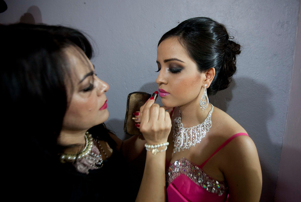 ". In this Jan. 26, 2013 photo, Magdabelyn Parra Gamez, who goes by Belyn, holds still as her lipstick is applied backstage as she competes in the ""Guamuchil Carnival Queen 2013\"" beauty pageant in Guamuchil, Sinaloa state, Mexico.  Belyn, 18, took up the mantle on the pageant circuit after the death of her cousin beauty queen Maria Susana Flores Gamez, who in November 2012 died like a mobster\'s moll, carrying an AK-47 assault rifle into a spray of gunfire from Mexican soldiers. \""This is in memory of Susy,\"" Belyn whispered, shortly before winning the crown, \""In honor of her.\"" (AP Photo/Eduardo Verdugo)"