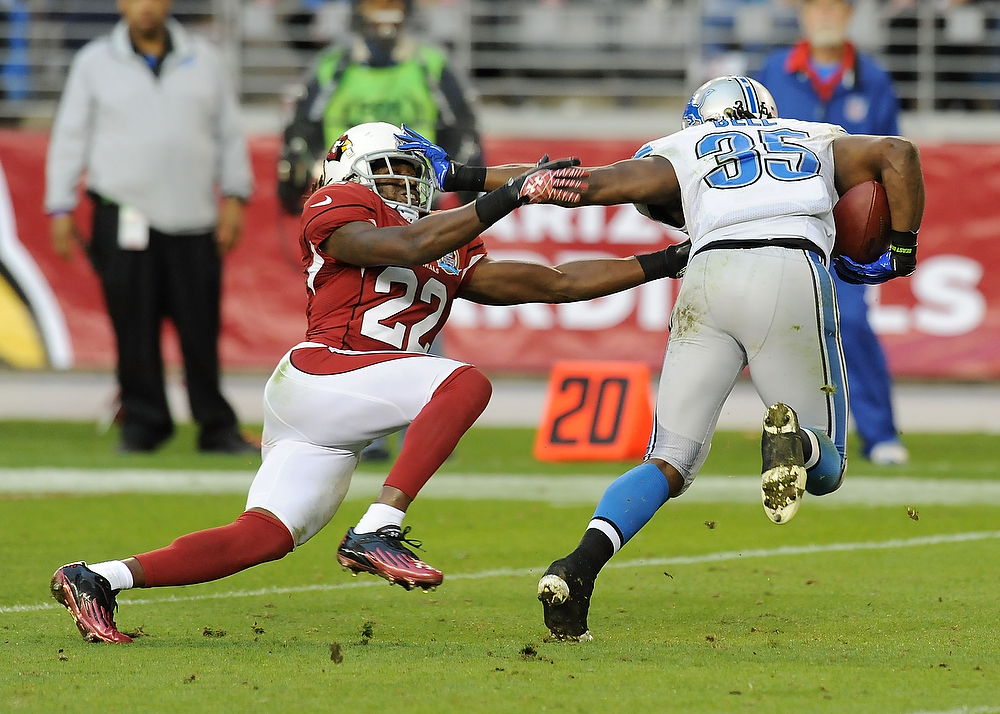 . Joique Bell #35 of the Detroit Lions straight arms William Gay #22 of the Arizona Cardinals at University of Phoenix Stadium on December 16, 2012 in Glendale, Arizona.  (Photo by Norm Hall/Getty Images)