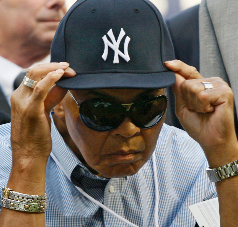 . Muhammad Ali adjusts a New York Yankees cap given to him by Yankees shortstop Derek Jeter before the Red Sox faced the Yankees in a baseball game at Yankee Stadium in New York, Thursday, Aug. 6, 2009. (AP Photo/Kathy Willens)