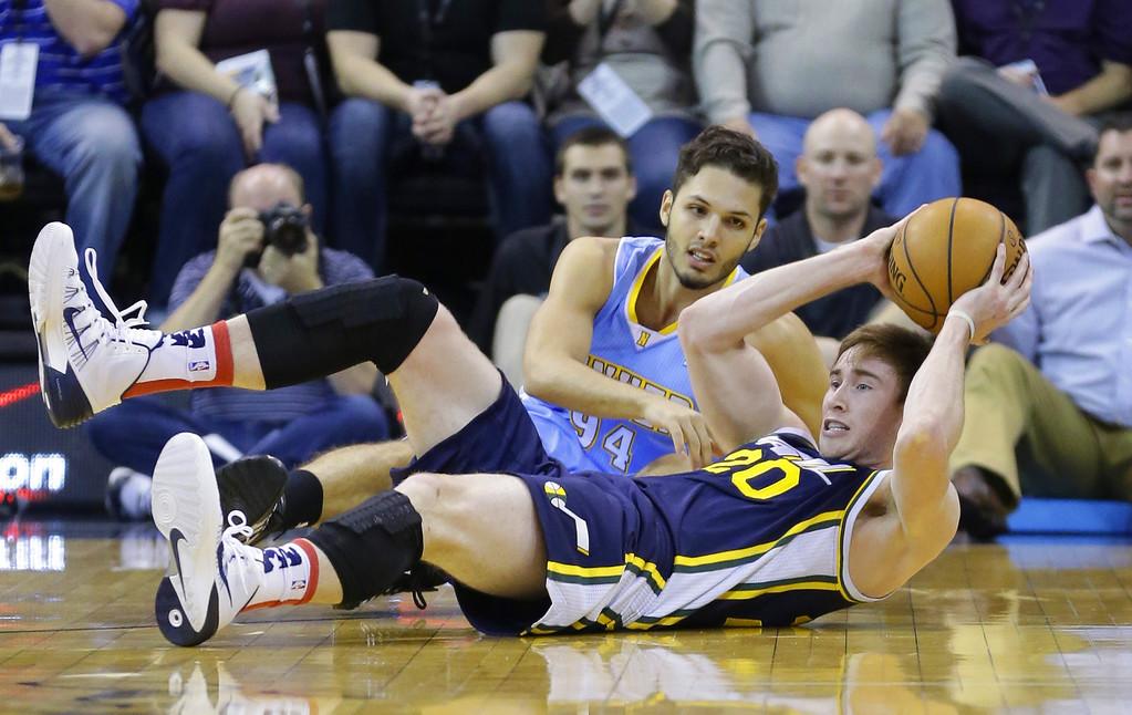 . Utah Jazz\'s Gordon Hayward (20) passes the ball as Denver Nuggets\' Evan Fournier (94) looks on in the first quarter during an NBA basketball game Monday, Nov. 11, 2013, in Salt Lake City.  (AP Photo/Rick Bowmer)