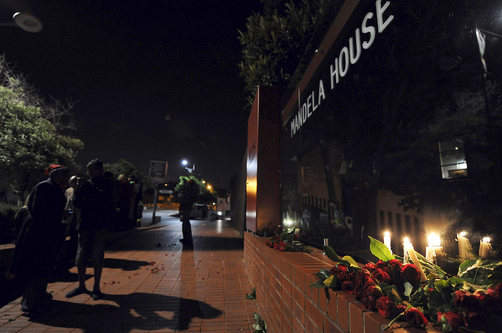 . Candles and flowers are placed outside former President Nelson Mandela\'s former home, now a museum, in Soweto, South Africa Friday, Dec. 6, 2013. South African President Jacob Zuma announced earlier that Mandela had died peacefully after a long  illness. (AP Photo)