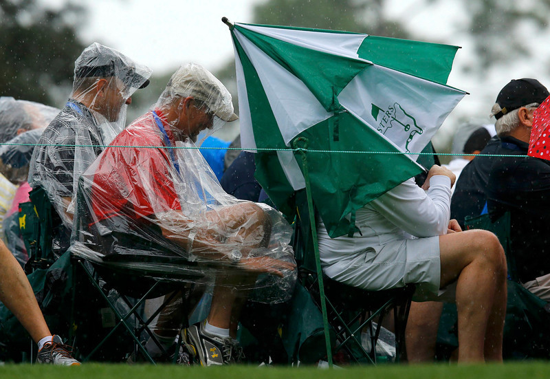 . Patrons protect themselves from the rain near the third green during second round play in the 2013 Masters golf tournament at the Augusta National Golf Club in Augusta, Georgia, April 12, 2013.   REUTERS/Brian Snyder