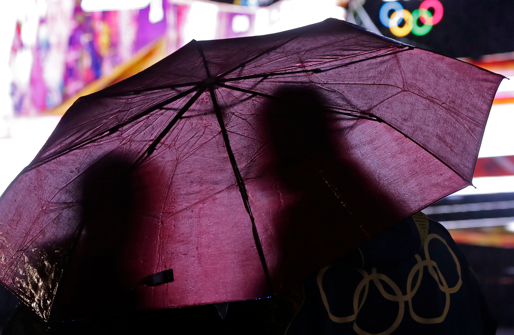 . Fans stand in the rain to watch a bobsled competition on a large video screen at the Sochi 2014 Winter Olympics, Tuesday, Feb. 18, 2014, in Krasnaya Polyana, Russia. (AP Photo/Charlie Riedel)