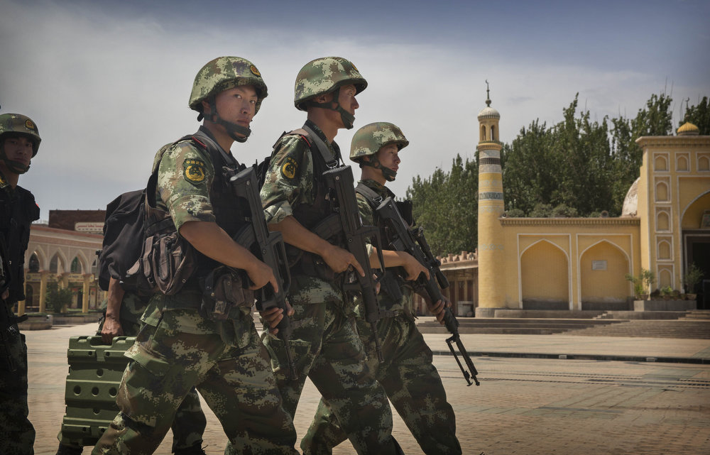 . KASHGAR, CHINA - JULY 31:  Chinese soldiers march in front of the Id Kah Mosque, China\'s largest, on July 31, 2014 in Kashgar, China. China has increased security in many parts of the restive Xinjiang province following some of the worst violence in months in the Uyghur dominated area.  (Photo by Getty Images)