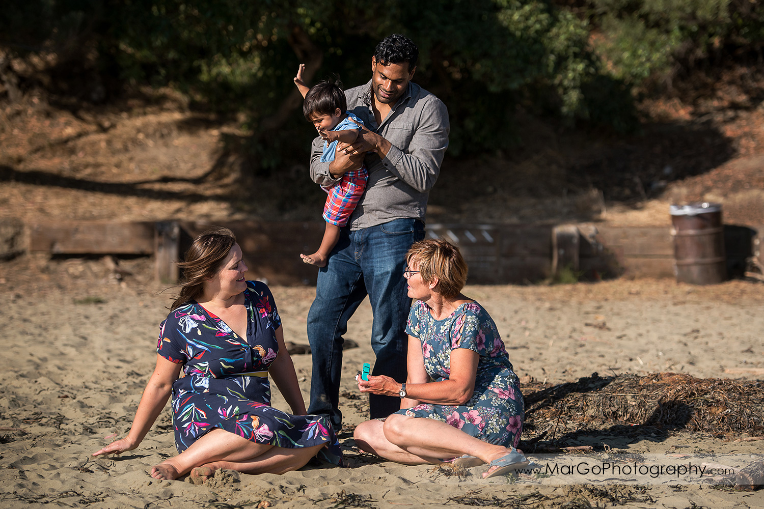 man in grey shirt holding little boy in blue shirt and red shorts standing behind two women in blue dresses with pink flowers sitting on the sand and at Richmond Keller Beach