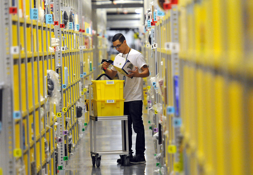 . Amazon\'s Robert Hammond, picks and scan merchandise to be send out during his shift at the fulfillment center in San Bernardino, CA., Oct. 28, 2013.  The Amazon Fulfillment Center opened up a year ago with only half of the facility operating for business, now with the the million-square-foot center complete they will host a grand opening on Tuesday, with Gov. Jerry Brown in attendance.  This distribution center has been celebrated in San Bernardino and at the state level as an example of job creation and growth. (John Valenzuela/Staff Photographer)  (John Valenzuela/Staff Photographer)