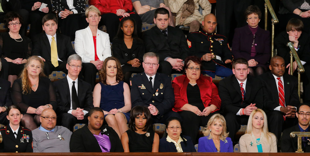 . First lady Michelle Obama, front row, center, and other, listen as President Barack Obama gives his State of the Union address during a joint session of Congress on Capitol Hill in Washington, Tuesday Feb. 12, 2013. Front row, from left are, Sgt. Sheena Adams, Nathanial Pendleton, Cleopatra Cowley-Pendleton, Mrs. Obama, Menchu Sanchez, Jill Biden, Kaitlin Roif and Alan Aleman.Second row, from from left are, Deb Carey, Apple CEO Tim Cook, Amanda McMillan, Lt. Brian Murphy, Marie Lopez Rogers and Bradley Henning. Third row, third from left are,Tracey Hepner, Haile Thomas, Lee Maxwell, Sgt. Carlos Evand and White House seniot adviser Valerie Jarrett,  (AP Photo/J. Scott Applewhite)