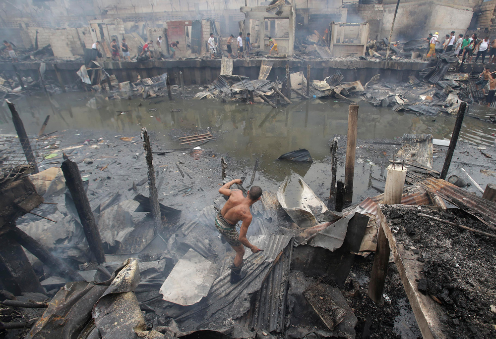. A Filipino man tries to retrieve items from still smoldering homes after a fire broke out at a slum area in Pasay, south of Manila, Philippines on Wednesday, July 24, 2013. Pasay City Fire Marshall Major Douglas Guiyab said about 250 houses were gutted in the area and the cause of the fire is still being determined. (AP Photo/Aaron Favila)