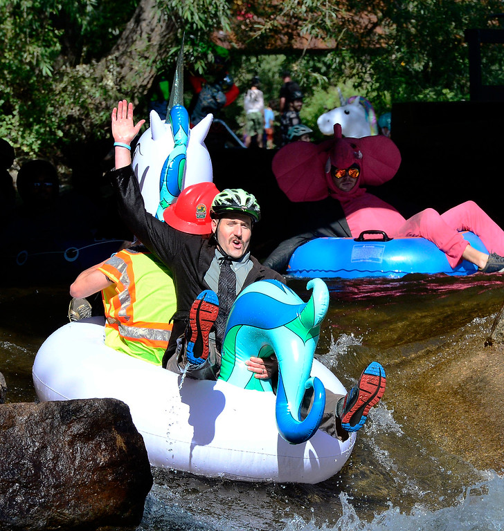 . Ryan Sohlden, rides a unicorn raft on Tube to Work Day, on Boulder Creek at the finish in Central Park on Wednesday morning.  Paul Aiken Staff Photographer July 11 2018