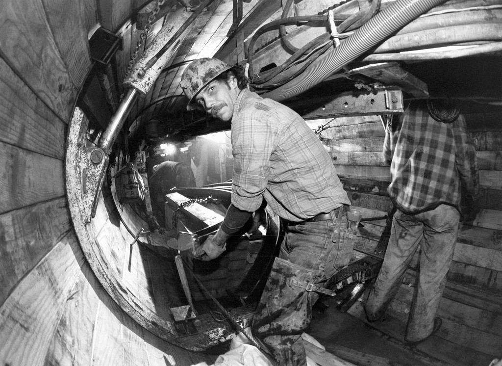. Mike Bray unloads the lumber and steel used to build the framework inside the Eklutna tunnel in Anchorage  Jan. 23, 1987. One the framework is completed, a 54-inch concrete pipe will be slipped inside to carry water to Anchorage. (AP Photo/Rob Stapleton)