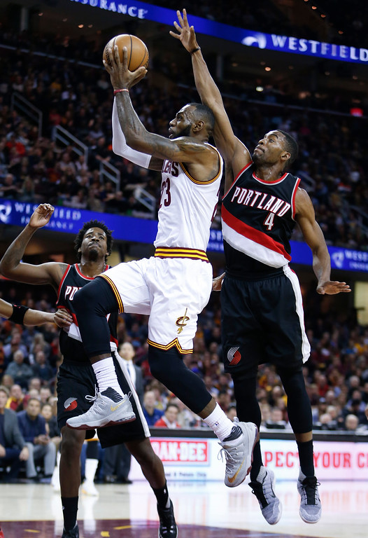 . Cleveland Cavaliers\' LeBron James (23) scores between Portland Trail Blazers\' Maurice Harkless (4) and Ed Davis (17) during the first half of an NBA basketball game, Wednesday, Nov. 23, 2016, in Cleveland. (AP Photo/Ron Schwane)