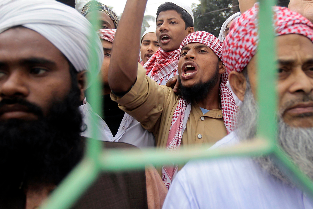 Description of . Activists of Islamic political parties shout slogans as they try to enforce a half-day nationwide strike in Dhaka, Bangladesh, on Thursday, Dec. 20, 2012. More than two dozen Islamic parties in Bangladesh want the country to be governed by Sharia, or Islamic law. A coalition of five leftist parties want the Islamic parties to be banned because they oppose the constitutional provision that says Bangladesh be governed by secular law. (AP Photo/A.M. Ahad)