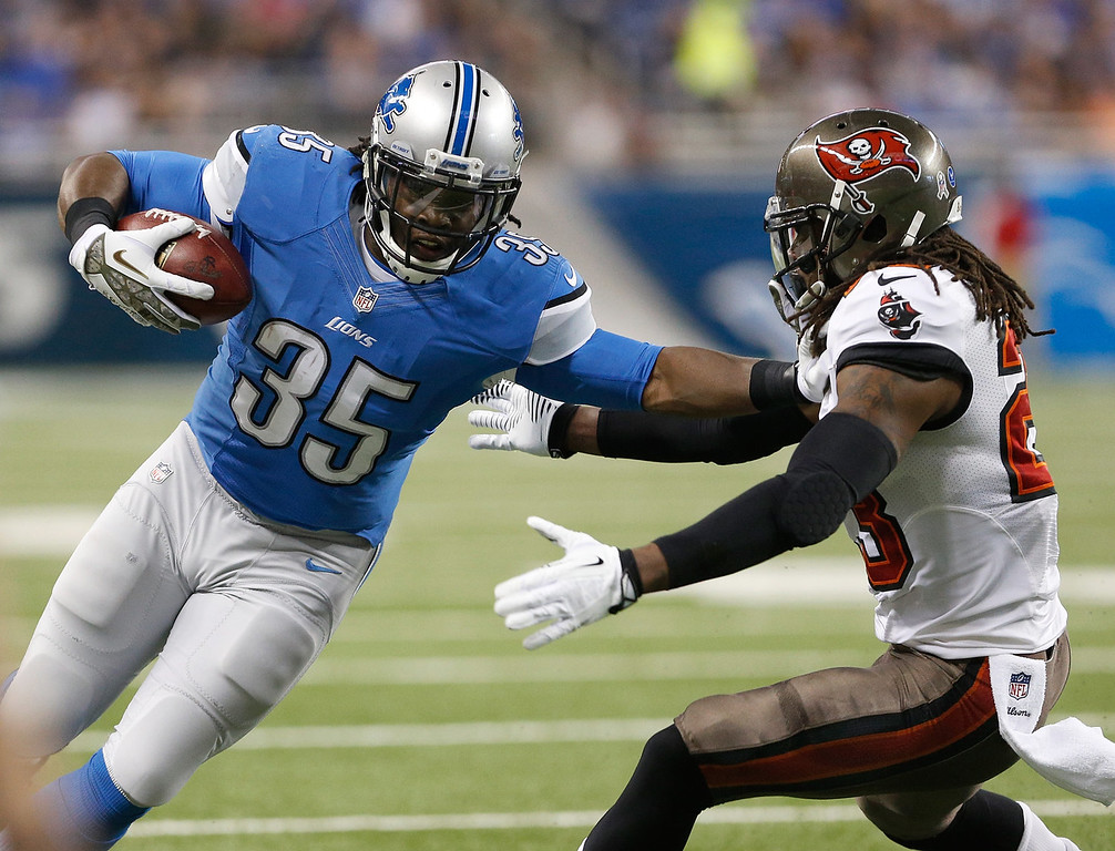 . Joique Bell #35 of the Detroit Lions stiff arms Mark Barron #23 of the Tampa Bay Buccaneers at Ford Field on November 24, 2013 in Detroit, Michigan. (Photo by Gregory Shamus/Getty Images)