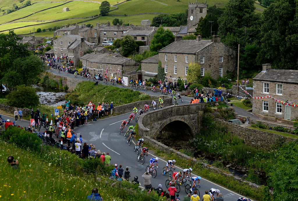 . The Peloton passes through the village of Muker, northern England  during the first day of 2014 Tour de France  Saturday July 5, 2014.  The 198 competitors in the 101st Tour de France have started their grueling three-week ride through four countries before ending the world\'s greatest cycling race in Paris on July 27. (AP Photo/Owen Humphreys)