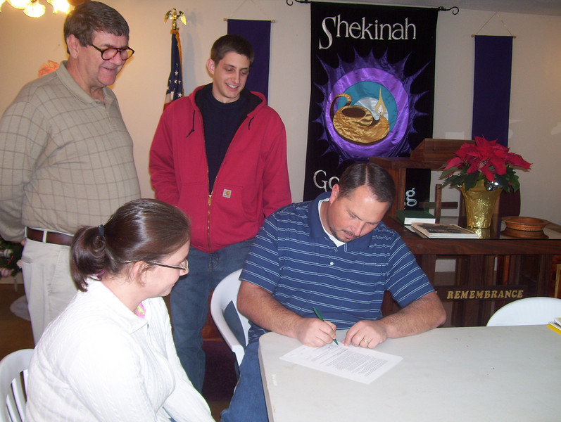 08 12-16 Fuller Center for Housing Director of U.S. Field Operations Glen Barton and Director of Special Programs Ryan Iafigliola look on as Covenant Agreement is signed by Mitch Vaughn. Board member Kari Wilcher is to his right. bb