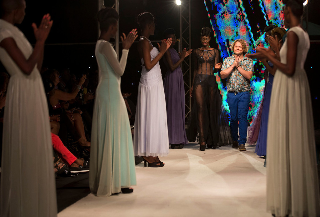 . Designer Evgheni Hudorojcov, center right, of Moldova walks along with models wearing his creations, at Hotel des Almadies, in Dakar, Senegal, in the early morning hours of Sunday, June 23, 2013. After a Friday show held in a dusty marketplace in the working class suburb of Guediawaye, the runway finale of Dakar Fashion Week was held at a luxury hotel and showcased the work of 14 designers from West Africa, Europe, South America, and the Caribbean. (AP Photo/Rebecca Blackwell)