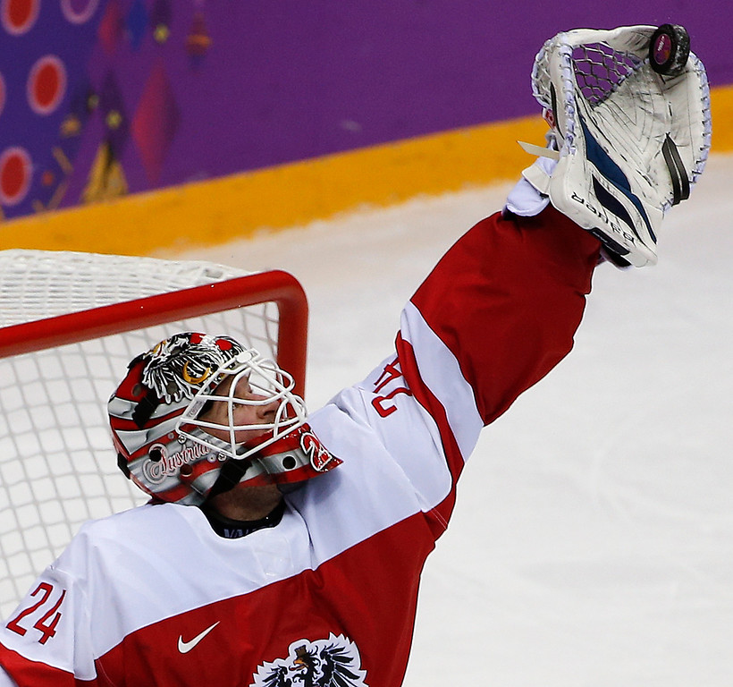 . Austria goaltender Mathias Lange snags a shot by Norway in the thirdperiod of a men\'s ice hockey game at the 2014 Winter Olympics, Sunday, Feb. 16, 2014, in Sochi, Russia. (AP Photo/Julio Cortez )