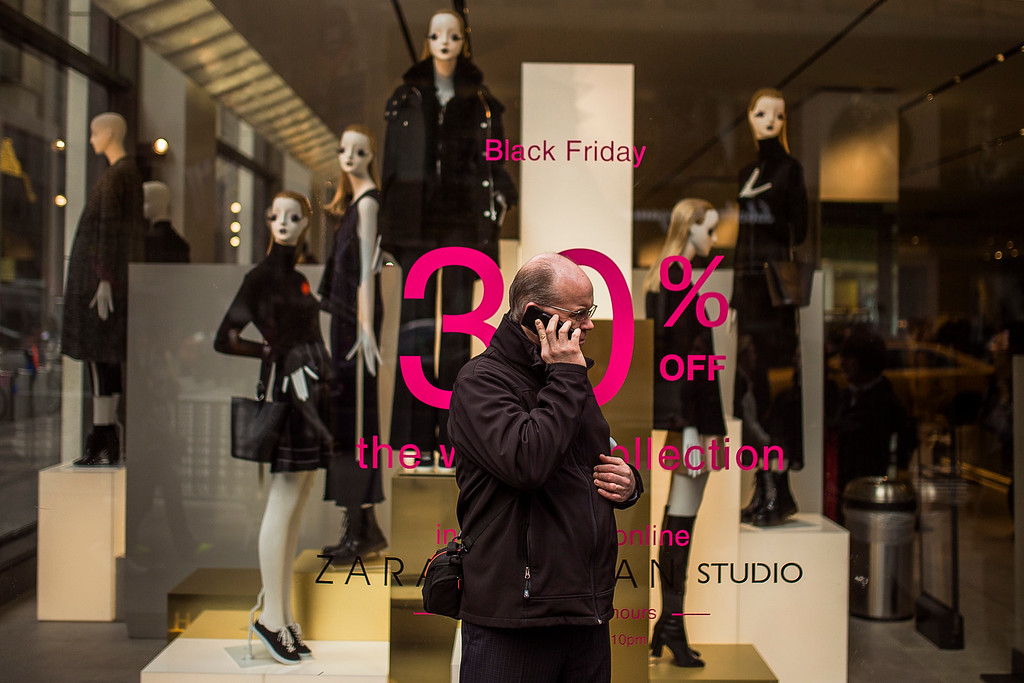 . A man speaks on a mobile phone in front of a retail showcase displaying discounts on Fifth Avenue on Black Friday in New York, Friday, Nov. 25, 2016. Shoppers were on the hunt for deals Friday as malls opened for what is still one of the busiest days of the year, even as the start of the holiday season edges ever earlier. (AP Photo/Andres Kudacki)