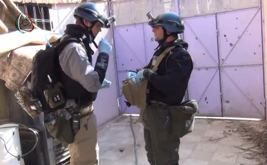""". An image grab taken from a video uploaded on YouTube by Moadamiyet al-Sham media centre on August 26, 2013 allegedly shows a United Nations (UN) arms experts inspecting the site where rockets had fallen in Damascus\' Moadamiyet al-Sham suburb as they investigate an alleged chemical weapons strike near the capital. The inspectors braved sniper fire but managed to gather what the UN called \""""valuable\"""" evidence from one site of last week\'s gruesome attacks in which hundreds are said to have been killed. -/AFP/Getty Images"""