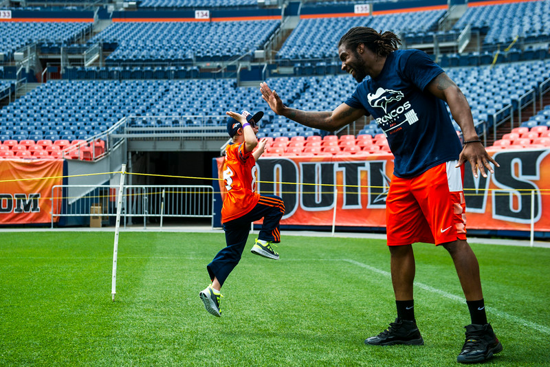 . Jaxson Schulte, 8, of Littleton jumps for a high five with David Bruton #30 of the Denver Broncos during the National Sports Center for the Disabled\'s Denver Broncos Ability Clinic at Sports Authority Field at Mile High on Tuesday, July 08, 2014 in Denver, CO. (Photo by Kent Nishimura/The Denver Post)