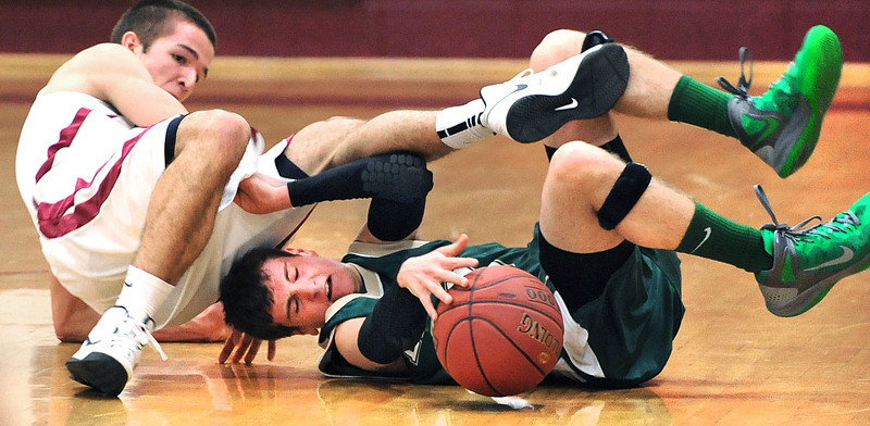 Rangeley's AJ Elmes, right and Richmond's Eddie Stewart roll to the ground as they battle for a loose ball during Tuesday night's boys varsity basketball game in Richmond.