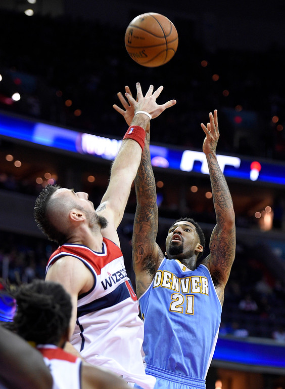 . Denver Nuggets forward Wilson Chandler (21) shootst against Washington Wizards center Marcin Gortat, left, of Poland, during the first half of an NBA basketball game, Friday, Dec. 5, 2014, in Washington. (AP Photo/Nick Wass)