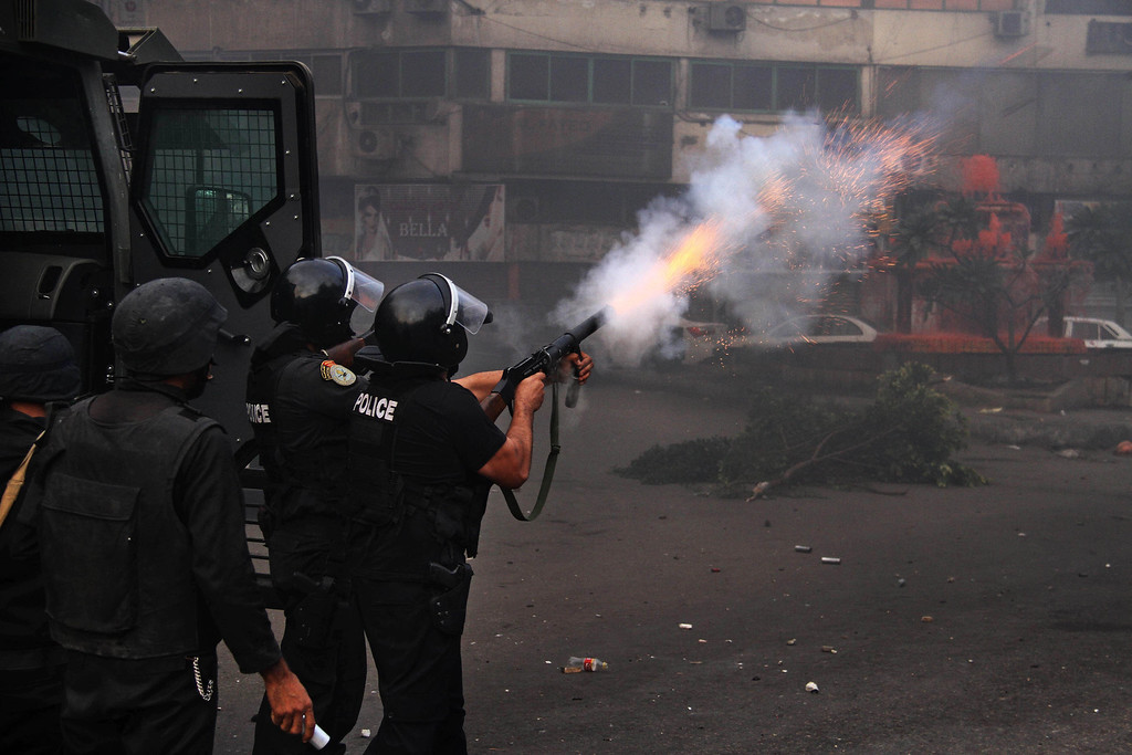 . Egyptian riot police fire tear gas in Cairo, Egypt, Friday, Nov. 29, 2013, to disperse hundreds of Islamist demonstrators defying a new protest law that has drawn widespread criticism from the international community and democracy advocates.(AP Photo/Ahmed Gomaa)