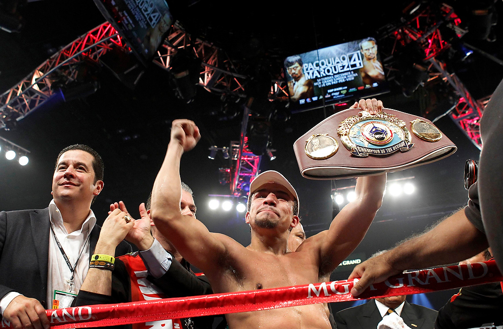 . Juan Manuel Marquez of Mexico celebrates his 6th round knock out victory over Manny Pacquiao of the Philippines during their welterweight fight at the MGM Grand Garden Arena in Las Vegas, Nevada December 8, 2012. Boxing promoter Fernando Beltran is at left. REUTERS/Steve Marcus