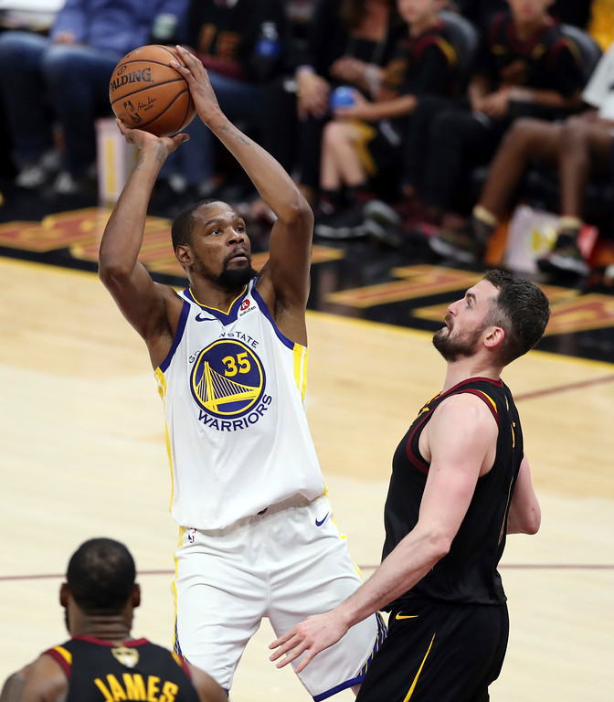 . Golden State Warriors\' Kevin Durant shoots over Cleveland Cavaliers\' Kevin Love during the second half of Game 3 of basketball\'s NBA Finals, Wednesday, June 6, 2018, in Cleveland. The Warriors defeated the Cavaliers 110-102 to take a 3-0 lead in the series. (AP Photo/Carlos Osorio)