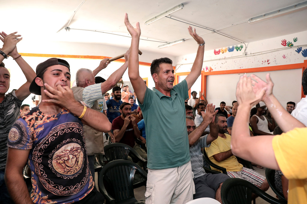 . Migrants supporting the Croatian national soccer team celebrate a goal as they watch on a TV set the final soccer match between Croatia and France during the 2018 soccer World Cup in Russia, at Ritsona camp, northeast of Athens, Sunday, July 15, 2018. (AP Photo/Yorgos Karahalis)